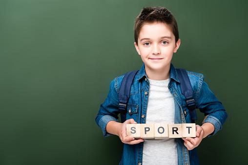 1016623732 istock photo schoolboy holding wooden cubes with word sport near blackboard 1016623700