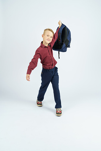 A schoolboy holds a schoolbag lifting it up. Education concept