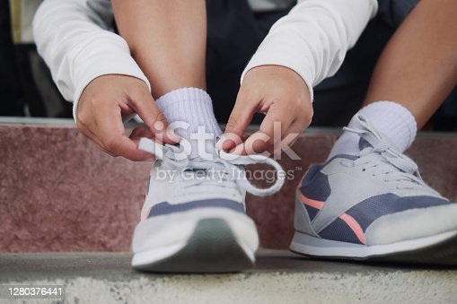 Schoolboy in casual clothing tying shoelaces on sneakers getting ready for school or traveling.