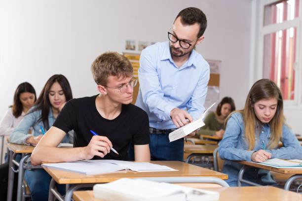Schuljunge schreibt Antwort auf die Frage auf Papier und Lehrer erklärt es – Foto