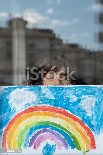 Portrait of schoolboy looking through window and posing with his watercolor rainbow painting. Reflection of city buildings is seen on window glass. Shot from outside of building with a full frame mirrorless camera.