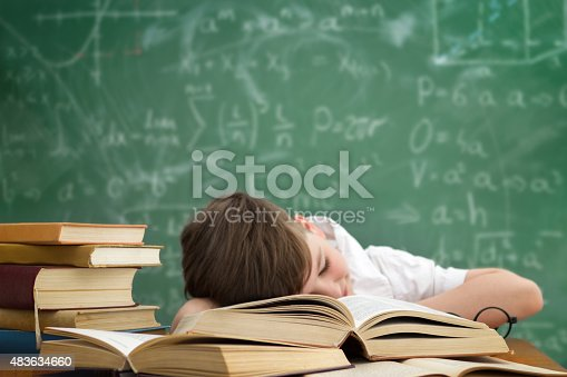 istock schoolboy lying and sleeping on book 483634660