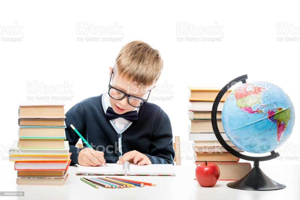 schooljongen potlood maakt notities in een notitieblok, in de buurt van een stapel boeken - Royalty-free Alleen kinderen Stockfoto