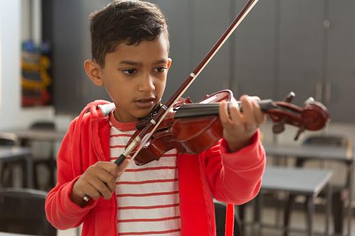 Schoolboy playing violin in classroom
