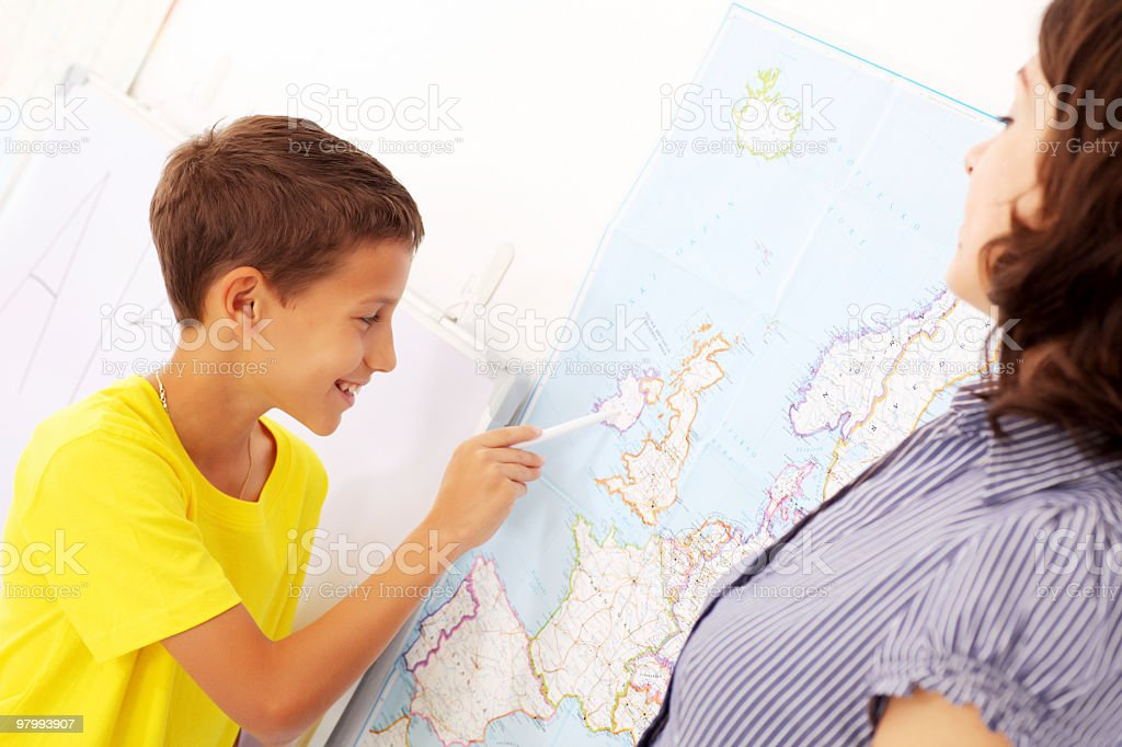 Schoolboy pointing to a map on geography lesson. royalty-free stock photo