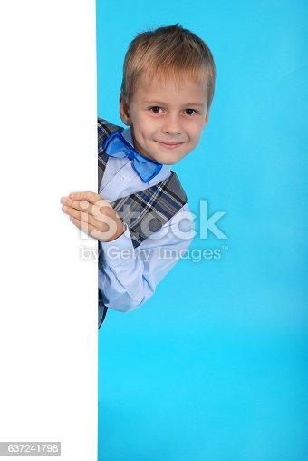 istock Schoolboy posing behind a white billboard 637241798