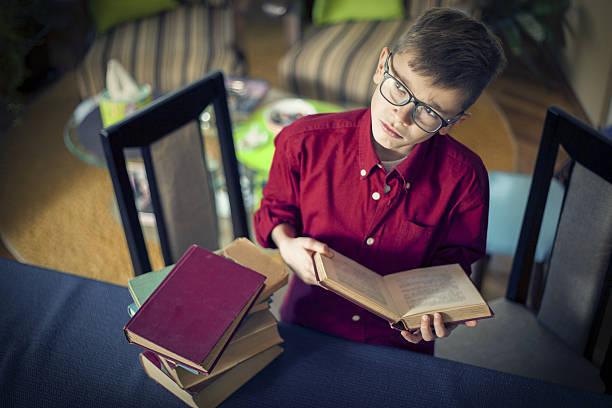 schoolboy reading a book and thinking - haushaltsbuch führen stock-fotos und bilder