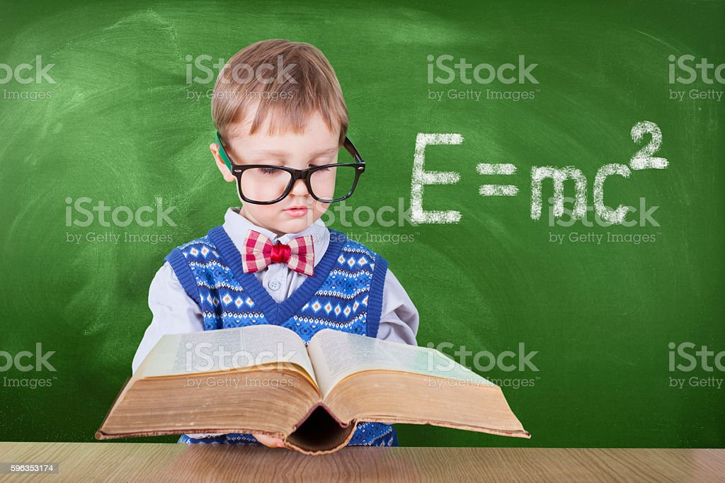 Schoolboy reading a book in front of school board royalty-free stock photo