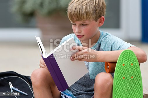 istock Schoolboy reading a book 521708789