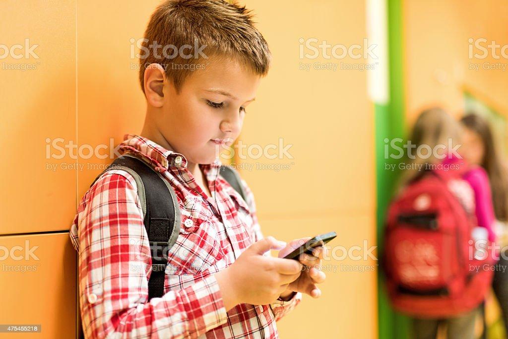 Schulkind-Nur Jungen lesen eine SMS auf Handy. – Foto