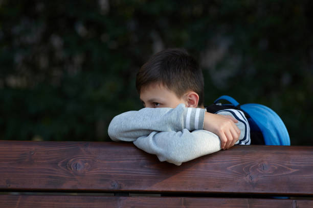 Schoolboy sits on a bench at a school park and cries stock photo