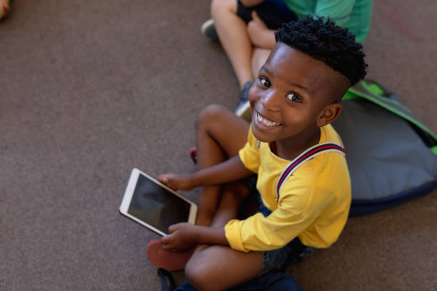Schoolboy sitting cross legged on the floor using a tablet computer in an elementary school classroo stock photo