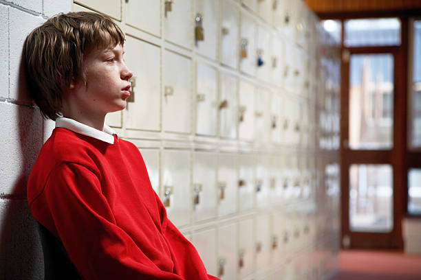 Schoolboy (11-13) sitting in corridor leaning head on wall, side view stock photo