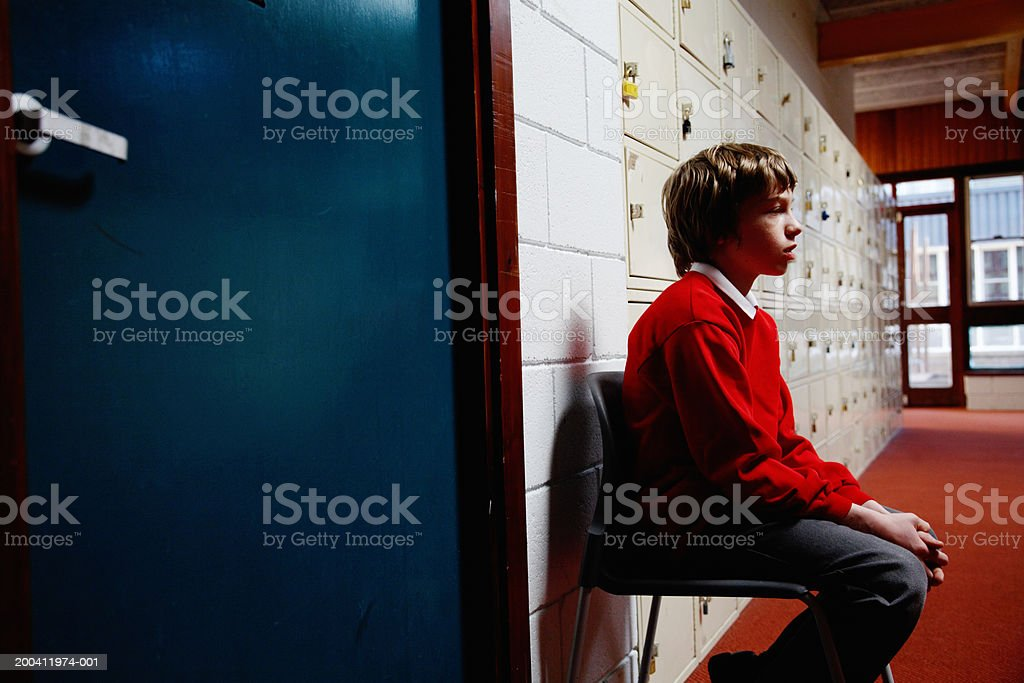 Schoolboy (11-13) sitting on chair in corridor, side view stock photo