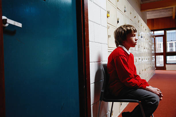 schoolboy (11-13) sitting on chair in corridor, side view - disbarment stock pictures, royalty-free photos & images