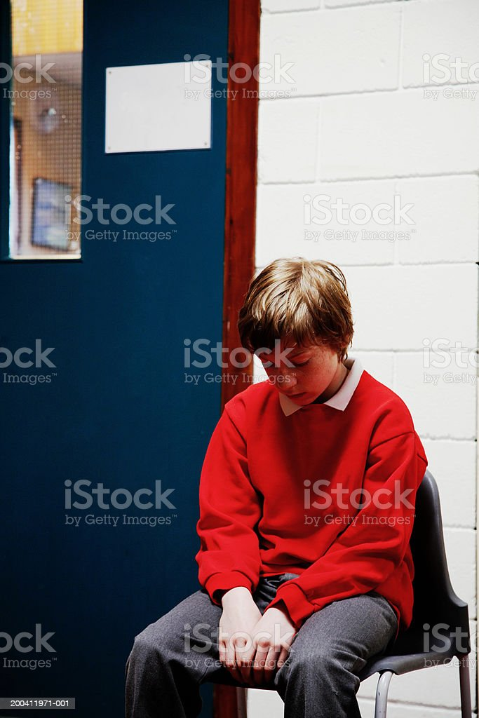 Schoolboy (11-13) sitting on chair outside classroom, head bowed stock photo