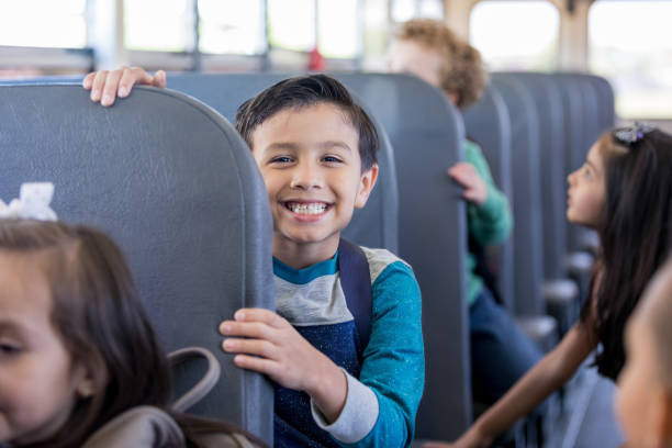 Schoolboy smiles excitedly while sitting on school bus While sitting on the school bus with other children, a young schoolboy smiles with anticipation at the camera. field trip stock pictures, royalty-free photos & images