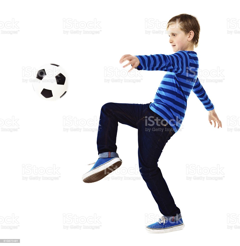 Schoolboy soccer player knees the ball stock photo