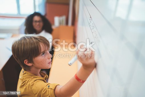 istock Schoolboy solving maths on whiteboard 1041789792