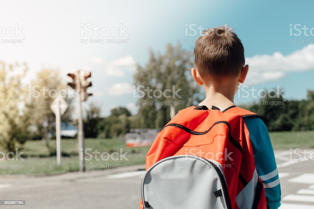 Schoolboy standing and waiting at zebra crossing stock photo