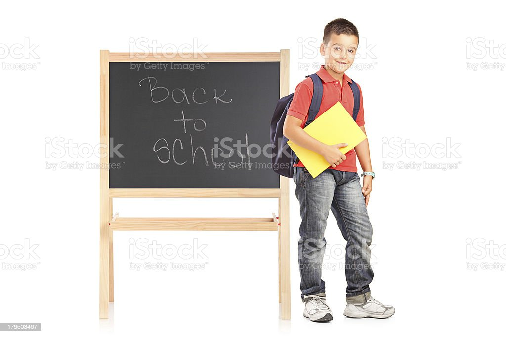 Schoolboy standing next to a school board royalty-free stock photo