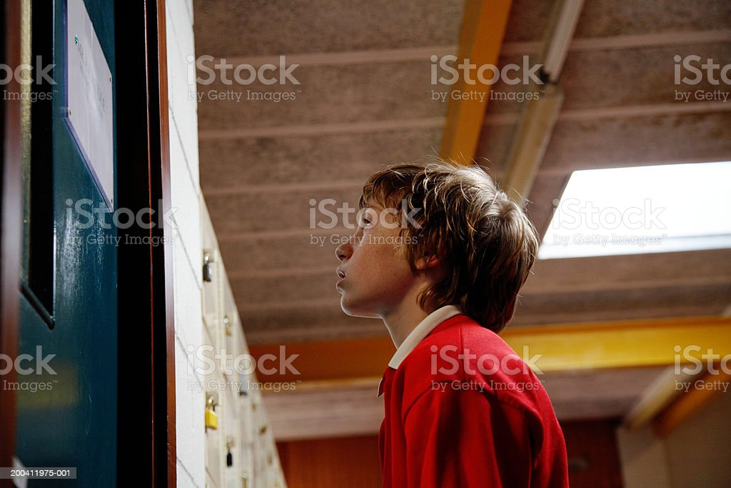 Schoolboy (11-13) standing outside door, low angle view  12-13 Years Stock Photo