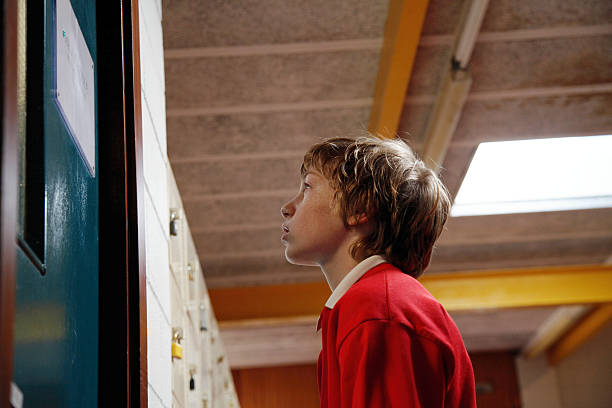 Schoolboy (11-13) standing outside door, low angle view stock photo