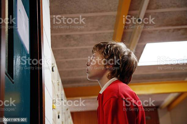 Schoolboy Standing Outside Door Low Angle View Stock Photo - Download Image Now