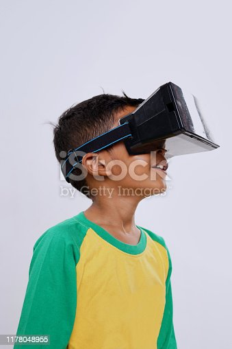 istock Schoolboy standing using virtual reality glasses on white background 1178048955