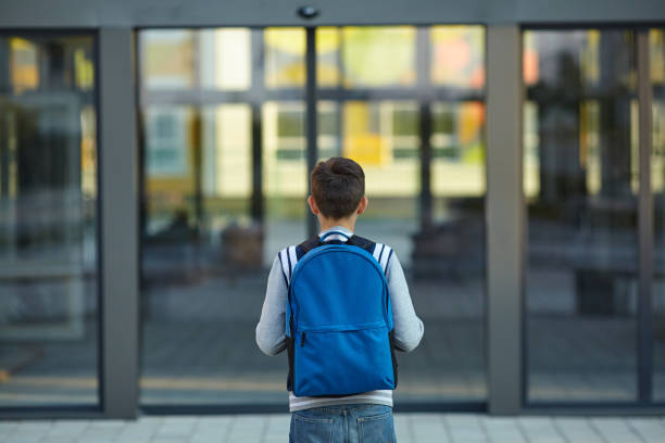 schoolboy stands in front of the school door - school building stock photos and pictures