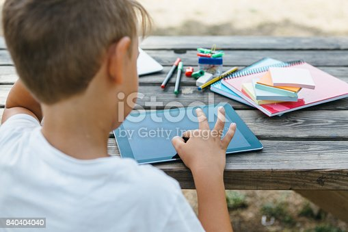 istock Schoolboy studying with tablet in garden 840404040