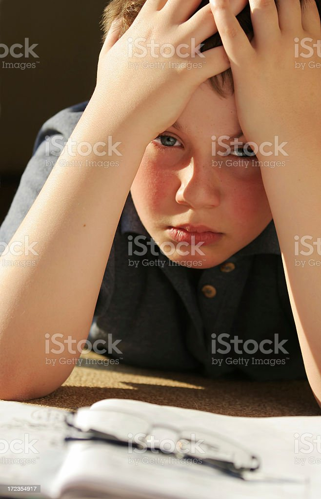 A schoolboy tiredly resting over his homework royalty-free stock photo