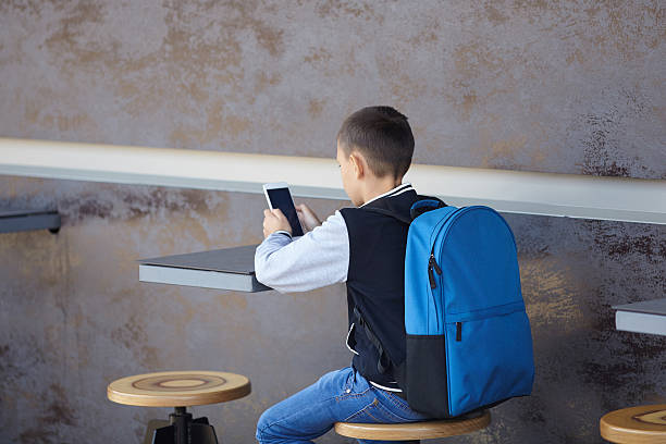 schoolboy using smartphone in cafe stock photo