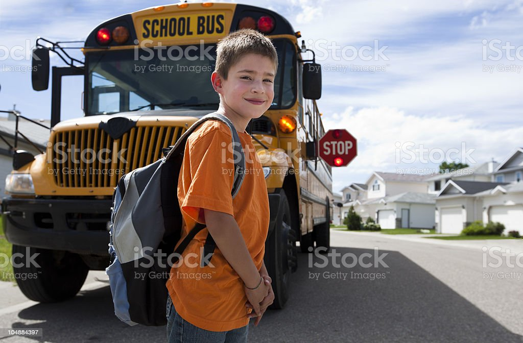 Schoolboy waiting to cross the street after departing bus royalty-free stock photo