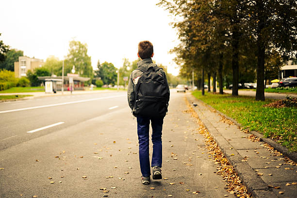 schoolboy walk alone stock photo