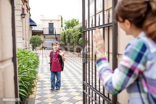 istock Schoolboy waving bye to his mother outside school 996998576