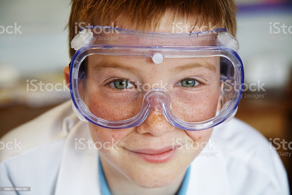 Schoolboy (11-13) wearing protective goggles, smiling, portrait  12-13 Years Stock Photo
