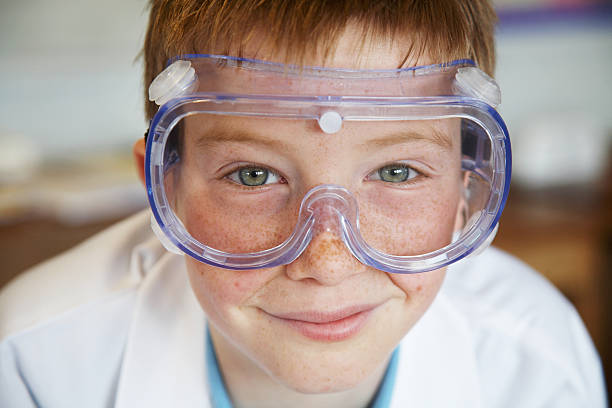 Schoolboy (11-13) wearing protective goggles, smiling, portrait stock photo
