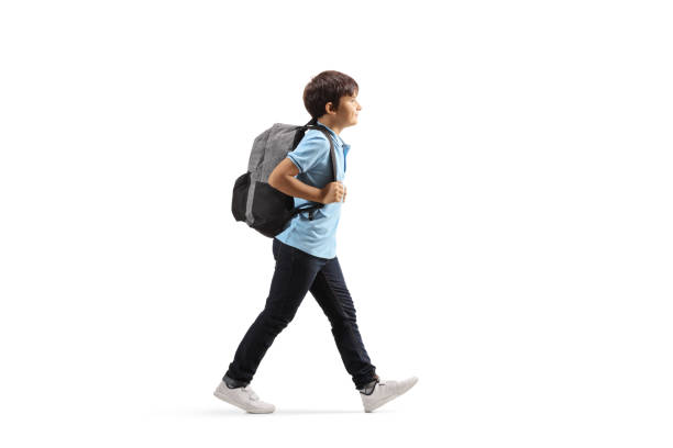 Schoolboy with a backpack walking Full length profile shot of a schoolboy with a backpack walking isolated on white background schoolboy stock pictures, royalty-free photos & images