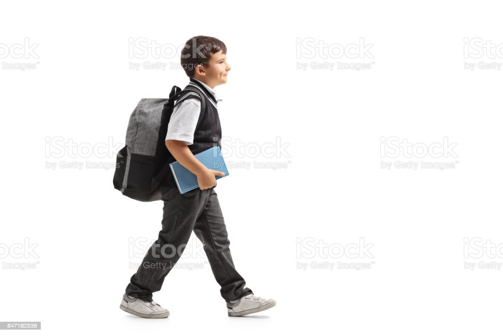 Schoolboy with a backpack walking stock photo