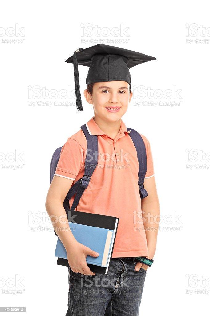 89e671c9d Niño en edad escolar con un sombrero de graduación sosteniendo libros foto  de stock libre de