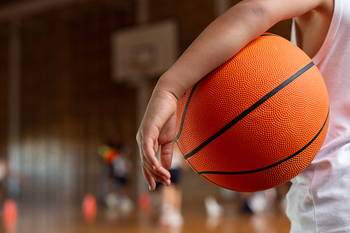 istock Schoolboy with basketball standing in basketball court 1133790384