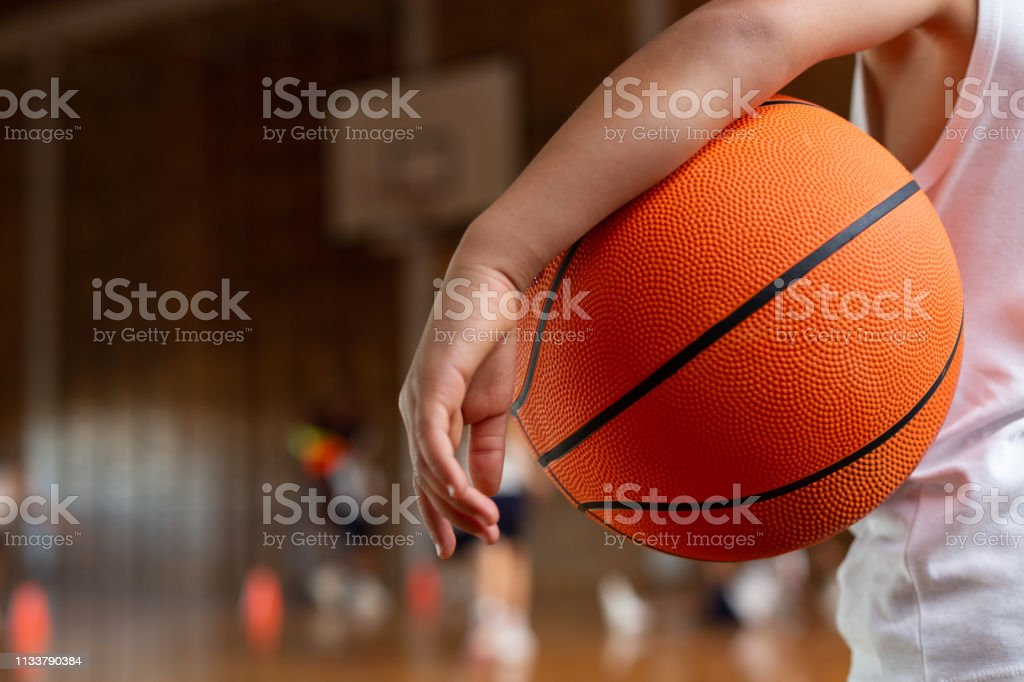 Schoolboy with basketball standing in basketball court stock photo