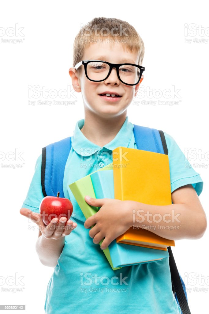schoolboy with books showing a red apple for lunch on a white background - Royalty-free Adolescence Stock Photo