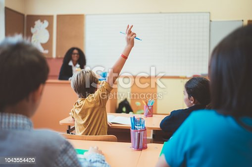 1160928955 istock photo Schoolboy with hand raised wants to answer teacher's question in class 1043554420