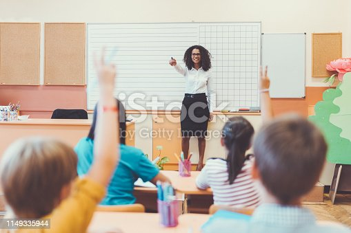 1160928955 istock photo Schoolboy with hand raised wants to answer teacher's question in class 1149335944