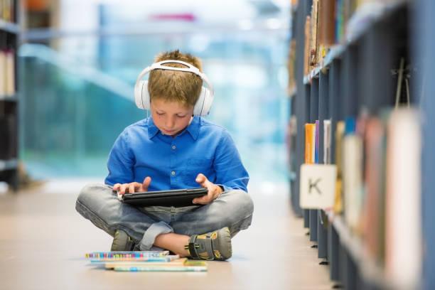 niño en edad escolar con auriculares y tableta digital sentado en la biblioteca piso - auriculares equipo de música fotografías e imágenes de stock