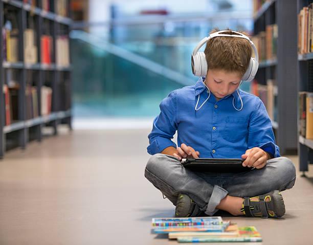 niño en edad escolar con auriculares y computadora de tableta en la biblioteca - auriculares equipo de música fotografías e imágenes de stock