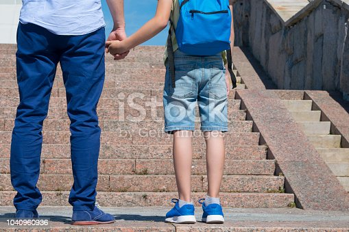 1045032684 istock photo schoolboy with his father are standing in front of the stairs upward, a boy is wearing a backpack 1040960936