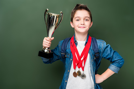 1016623732 istock photo schoolboy with medals holding winner cup near blackboard 1016623726